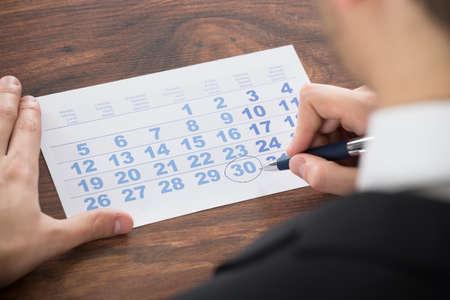 persona escribiendo: Primer plano del hombre de negocios marcado de la fecha en el calendario