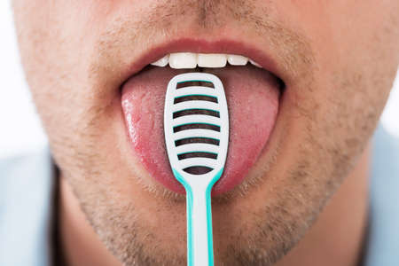halitosis: Close-up Of Young Man Cleaning His Tongue With Scraper