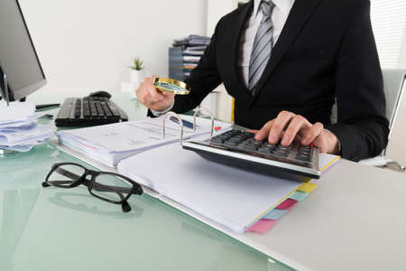 expenses: Photo Of Businessman Analyzing Bills With Magnifying Glass Stock Photo