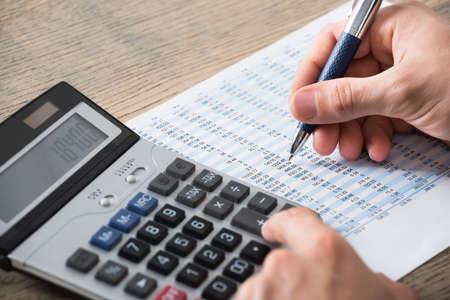 accounting records: Primer plano de un empresario Analizando documento contable con la calculadora en el escritorio en la oficina