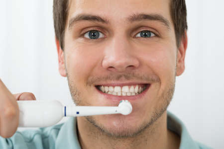 clean  electric: Close-up Of Young Man Brushing Teeth With Electric Toothbrush