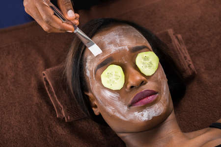 chemical peels: Close-up Of African Woman Applying Facial Mask In Spa