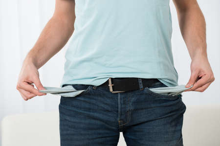 empty pockets: Close-up Of Young Man Showing Empty Pockets At Home Stock Photo