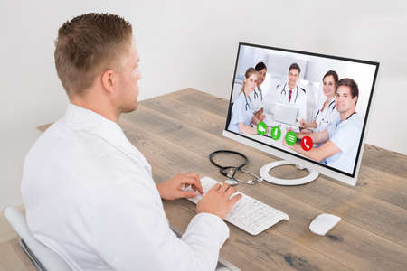 learning online: Young Male Doctor Video Conferencing With Medical Team On Computer Desk In Clinic