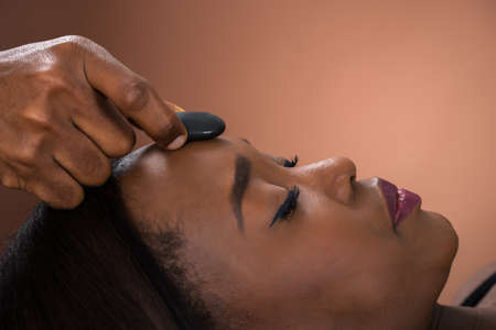 Close-up Of Young African Woman Receiving Hot Stone Massage At Spa Stock Photo