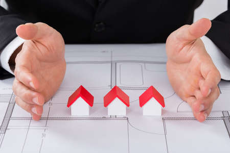 structural engineers: Close-up Of Male Architect Hand Protecting Different Size Of House Models On Blueprint Stock Photo