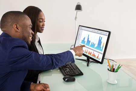 アフリカ系アメリカ人ビジネスの男性と女性コンピューター上、抜群のチームワークで表示 写真素材