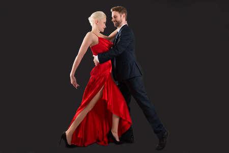 Portrait der jungen glücklichen Paar-Tanzen auf schwarzem Hintergrund