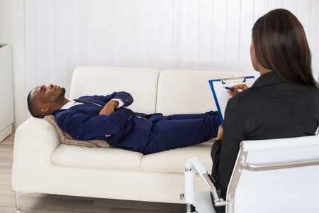 African American Man Laying On Couch In Front Of Psychiatrist With Clipboard Stock Photo