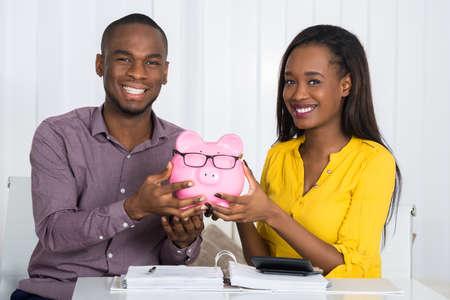 請求書と机の上の電卓 Piggybank を保持している幸せなカップル