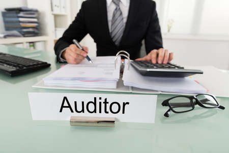 auditor: Photo Of Male Auditor Calculating Bill In Office Stock Photo
