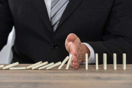 domino: Close-up Of A Businessman Hand Stopping Dominoes From Falling On A Desk In Office
