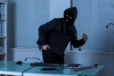 ladrón: Ladr�n que roba la computadora port�til y tableta digital en el escritorio de oficina