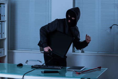 trespass: Thief Stealing Computer With Laptop And Digital Tablet On Office Desk Stock Photo