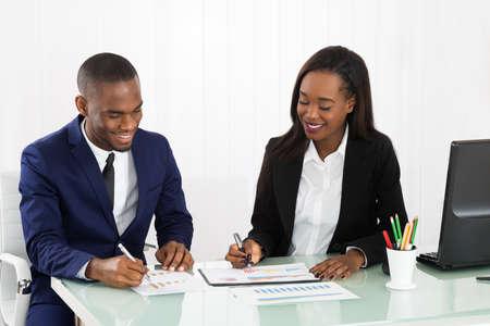 patron: Los empresarios que discuten tablas y gráficos que muestran los resultados de su equipo con éxito