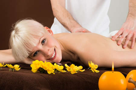 spa woman: Smiling Young Woman Receiving Shoulder Massage From A Massager In A Beauty Spa