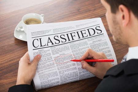 Homme d'affaires Mise en évidence Publicité Sur journal Avec Red Pen