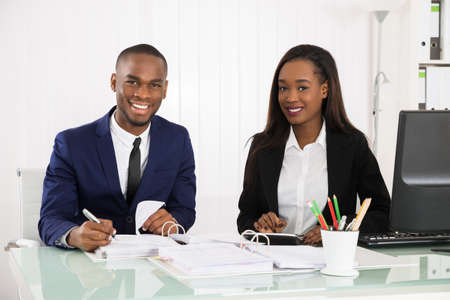 bank manager: Two Happy Businesspeople Working On Business Document At Office Stock Photo