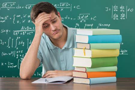 agotado: Hombre joven triste que mira la pila de libros en el escritorio