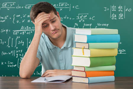 exhausted: Sad Young Man Looking At Stack Of Books At Desk