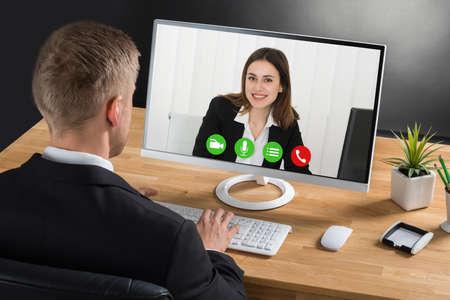 El hombre de negocios joven Videoconferencia Con colega en la computadora portátil en el escritorio en la oficina
