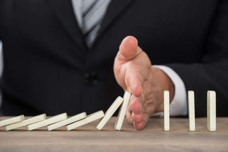 dominoes: Close-up Of A Businessman Hand Stopping Dominoes From Falling On A Desk In Office