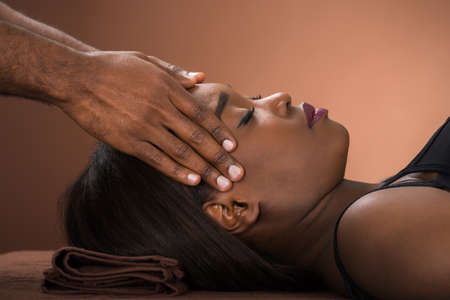 Receiving: Relaxed Young African Woman Receiving Forehead Massage In Spa