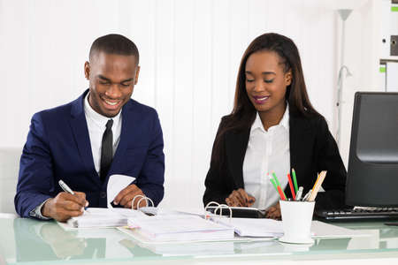 smiling businessman: Two Happy Businesspeople Working On Business Document At Office Stock Photo