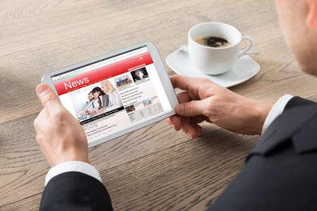 Primer plano del hombre de negocios lectura de noticias en la tableta digital en Oficina