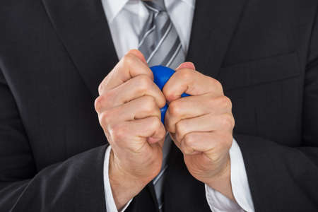 stress ball: Close-up Of Businessman Pressing Stress Ball In Office
