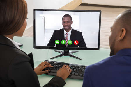 Two Businesspeople Having Videoconference On Computer At Office Stock Photo