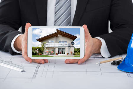 structural engineers: Close-up Of Young Male Architect Showing House On Digital Tablet Over Blueprint In Office