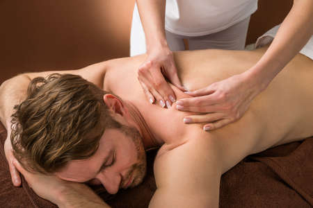 male massage: Portrait Of A Young Man Receiving Back Massage At A Beauty Spa Stock Photo