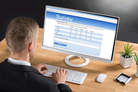 Close-up van jonge zakenman Het vullen Online Survey formulier computer op het bureau