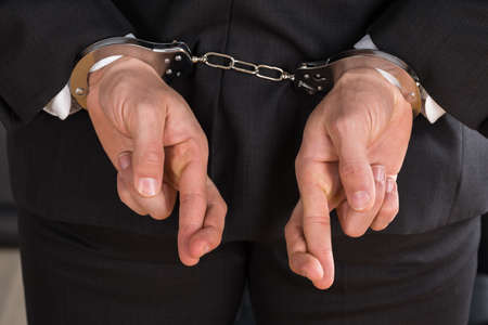 criminal defense: Close-up Of Businessman With Handcuffs And Finger Crossed. Crossed Fingers As A Symbol Of Breach Of Contract