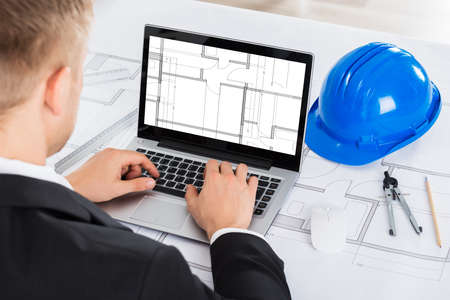 Male Architect Analyzing Blue Print On Computer Over Blue Print In Office Stock Photo
