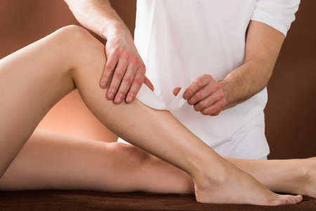 depilate: Close-up Of A Woman Getting Her Leg Waxed By Applying Wax Strips At Beauty Spa