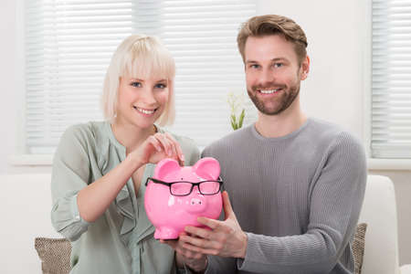 Young Happy Couple Sitting On Sofa Inserting Coin At Piggybank Stock Photo