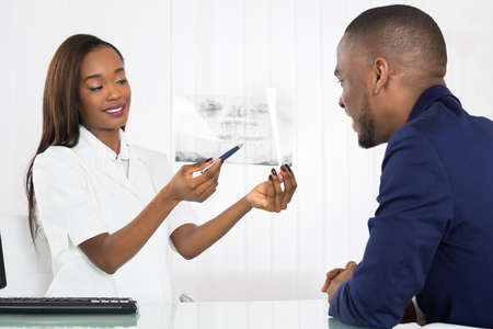 a medical examination: African American Woman Dentist Showing X-rays To Patient In Diagnostic Center Stock Photo