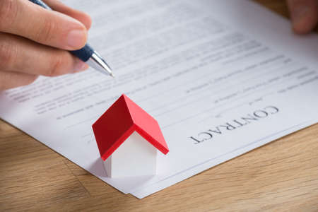 home loan: Close-up Of Businessman Holding Pen On Contract Paper With House Model On It Stock Photo