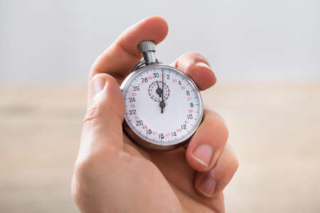 timekeeping: Close-up Of Businessman Holding Stopwatch In Office