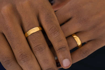 Close-up Of African Hands Wearing Golden Rings Stockfoto