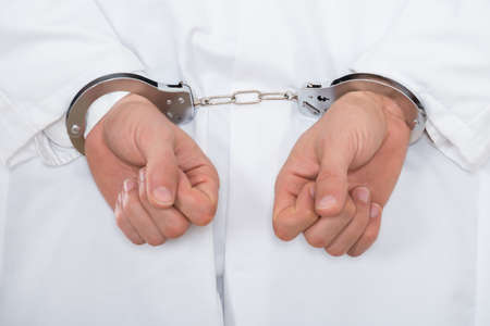 deceitful: Close-up Of Male Arrested Doctor Hand With Handcuffs Stock Photo