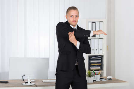 corporate office: Portrait Of A Young Businessman Stretching In Office Stock Photo
