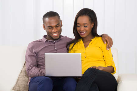 couple on couch: Happy Young Couple Sitting On Couch Using Laptop