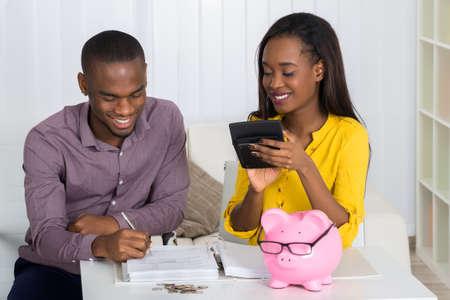 calculadora: Feliz Pareja Joven Cálculo de Bill con las monedas y Piggybank En El Escritorio Foto de archivo