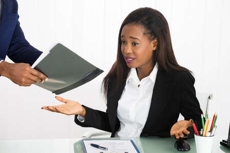 Boss Showing Document To Frustrated Female Worker In Office