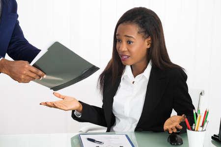 acoso laboral: Jefe muestra el documento a Frustrado Trabajador de sexo femenino en oficina