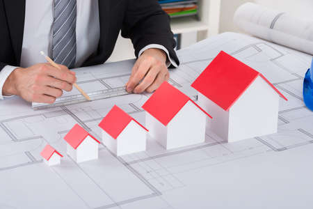 measuring: Close-up Of Male Architect Hand With House Models Working On Blueprint In Office
