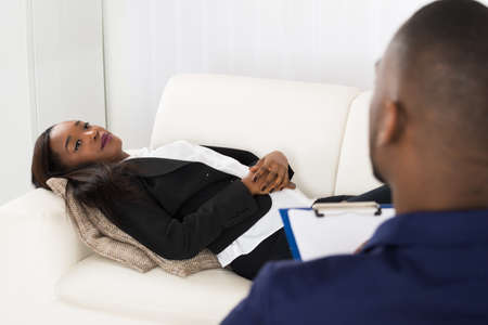 health woman: African American Woman Laying On Couch In Front Of Psychiatrist With Clipboard Stock Photo